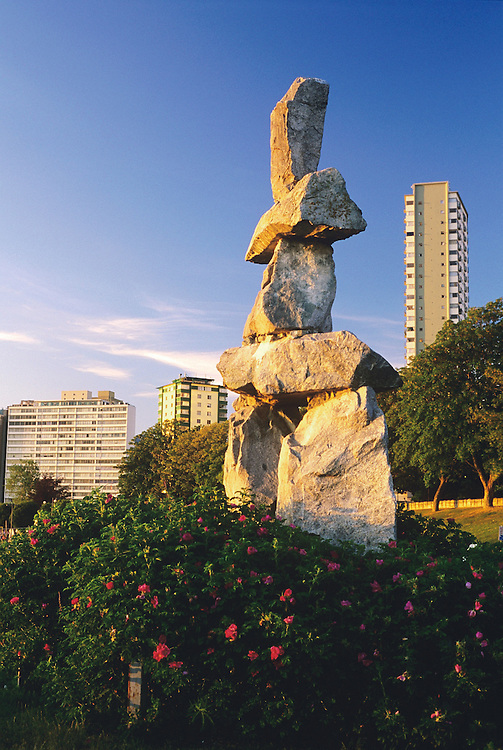 Inukshuk statue, wild roses, and apartment towers at English Bay in the West End of Vancouver, BC.