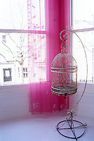 An antique birdcage stands against a bright pink curtain in the bay window of a white-painted London apartment