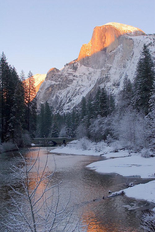 The final glow of winter's sun warms the vertical walls of Half Dome in Yosemite valley.  Below the Merced River flows quietly through the cold blue colors of winter.