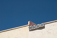 A woven blue and  rug hangs over a white roof-top wall against a blue sky, Fez, Morocco.