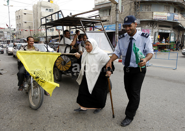 A Palestinian woman waves the Fatah party flag as she is helped to cross the street by a Hamas security man during celebrations to mark the political reconciliation agreement during a rally in Rafah, southern Gaza Strip, on May 4, 2011 as Palestinians in the West Bank and Gaza Strip gather to welcome a reconciliation deal signed by rival movements Hamas and Fatah in Cairo. Photo by Abed Rahim Khatib