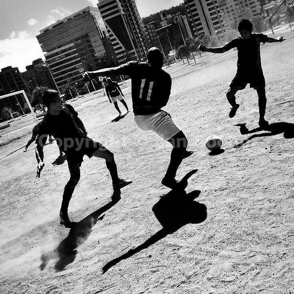 Ecuadorian men play football on a dirt football pitch in Parque La Carolina, a park in the central business district of Quito, Ecuador, 1 October 2014.