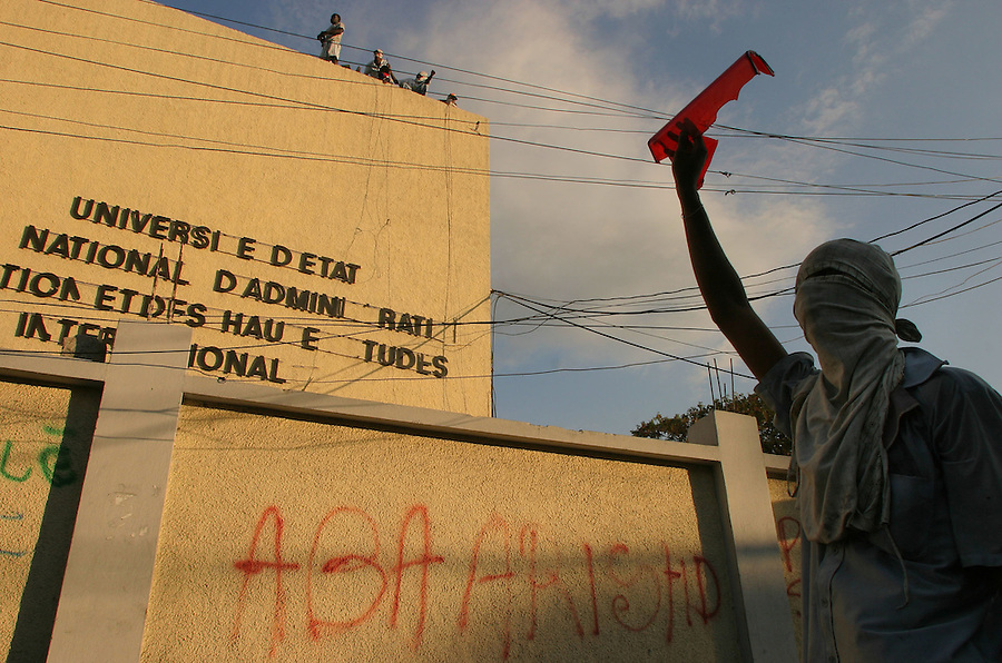 A masked student holds up a shard of tail light broken from a police truck as students engaged in a game of cat and mouse throwing rocks and bottles at police in riot gear riding a truck repeatedly through the streets surrounding the University of Haiti on Saturday February 21, 2004.  The clash took place  in the context of the violent suppression the previous day of a student protest by pro-Aristide miltias during the police took no action. (Credit: Lucian M. Read/World Picture News)