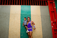 "Maximo a Lucha Libre wrestler, an ""Exotico"", meaning he fights as a gay Luchador poses with his eldest son in the hallway of Arena Mexico. Mexico City"