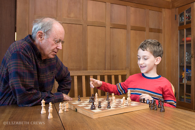 Berkeley CA Grandfather, seventy-six, playing chess with exultant, winning, grandson, six-years-old MR