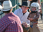 Weston Starr, 2, of Fallon waits with his uncle Blaine Tibbals for the start of the mutton bustin' event at the Smackdown Tour at Fuji Park in Carson City, Nev., on Saturday, June 7, 2014.<br /> Photo by Cathleen Allison