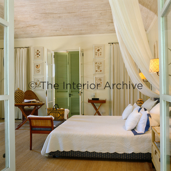 One of several comfortably furnished guest bedrooms with shuttered doors leading onto the terrace