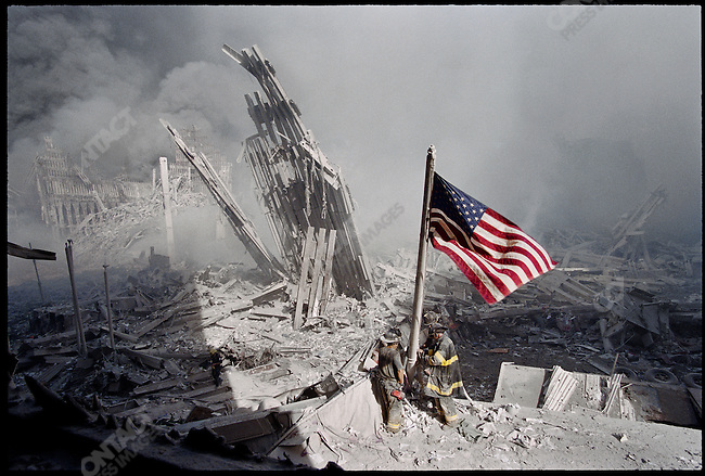 Firemen raising an American flag, in the wreckage of the World Trade Center, after the terrorist attack of September 11. New York City, NY, USA, September 11, 2001
