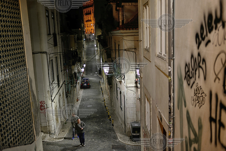 Two men wander along one of the typical steep back streets of the capital.