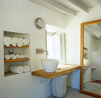 Rolled up white towels are stored on shelves next to a wash basin and long mirror in this simple bathroom