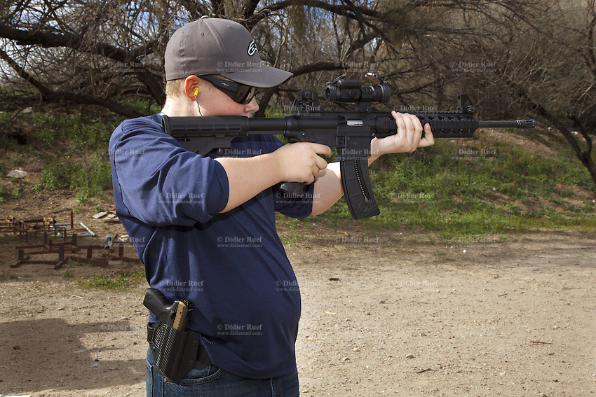 USA. Arizona state. Kearny town. Copper Basin Sportsmen's Club. Chance Stonecipher, 13 years old, is a teenage boy. He is training  his shooting skills with a Smith & Wesson M&P15-22 which is a semi-automantic rifle. The adolescent carries also on his belt a holster with a pistol Ruger SR22. Copper Basin Sportsmen's Club is a membership Range complex which purpose is to promote the sport of shooting and providing a safe, fun, family oriented environment. A firearm is a portable gun, being a barreled weapon that launches one or more projectiles often driven by the action of an explosive force. Most modern firearms have rifled barrels to impart spin to the projectile for improved flight stability. The word firearms usually is used in a sense restricted to small arms (weapons that can be carried by a single person). The right to keep and bear arms is a fundamental right protected in the United States by the Second Amendment of the Bill of Rights in the Constitution of the United States of America and in the state constitutions of Arizona and 43 other states. 29.01.16 © 2016 Didier Ruef