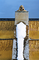 A gilded frog on a stone buttress overlooks a snow-covered wall