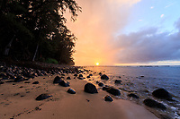 The sun sets through the mist and rain on a sandy beach with black volcanic rocks in between Ke'e and Ha'ena Beach Parks on Kaua'i.