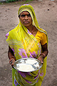 An anganwadi centre worker poses for a portrait with a plate full of mid-day meal (wheat flour+soya) that is given to young children at the Anganwadi centre in village Bachauli, outskirts of Jhansi, Uttar Pradesh, India. The Indian government spends $1.4 billion a year - on programs that include weighing newborn babies, counseling mothers on healthy eating and supplementing meals, but none of this is yeilding results. According to UNICEF, some 48% of Indian children, or 61 million kids, remain malnourished, the clinical condition of being so undernourished that their physical and mental growth are stunted. Photo: Sanjit Das/Panos for The Wall Street Journal.Slug: IMALNUT