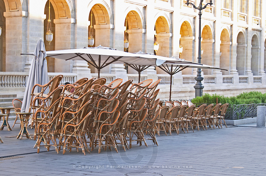 A cafe. Chairs and tables piled up for closing. Le Grand Theatre theatre and opera house on Place De La Comedie. Bordeaux city, Aquitaine, Gironde, France