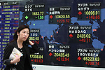 May 13, 2010 - Tokyo, Japan - A pedestrian walks past an electronic stock board at the Tokyo Stock Exchange in Tokyo, Japan, on May 13, 2010. Tokyo stocks rose the most in two weeks as more companies raised their profit forecasts and after Spain's deficit reduction plan eased worries about Europe's debt mountain and good economic news sent U.S. stocks sharply higher.