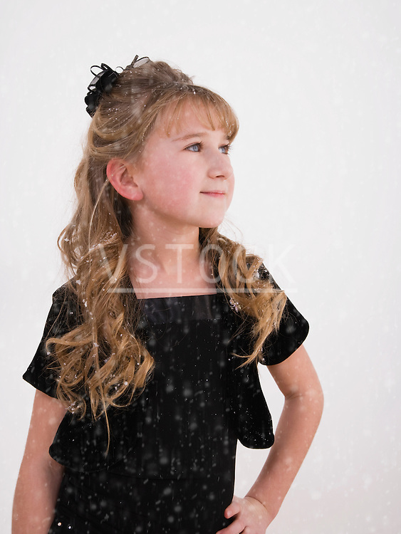 Girl (7-10) with hand on hip, smiling in snow