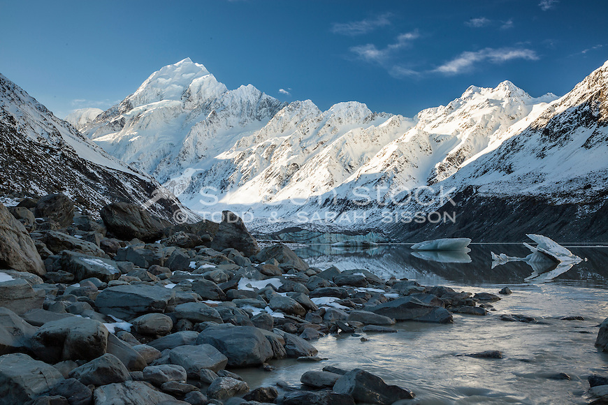 Hooker Lake in late Autumn.  Hooker River in foreground. National Park New Zealand. Small icebergs in lake. Aoraki Mt Cook National Park New Zealand.