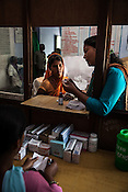 Rajkumari Chaudhary, the local Female Community Health Worker explains the medicine dosage to 25 year old Dayawati for her 17 month son, Naresh Mukhiya waits at the local health centre in Hanuman Nagar in Saptari, Nepal. <br /> Naresh Mukhiya was first admitted on July 17, 2013 when he was 9 months old. MUAC - 109 mm, Weight - 5.5kg, and Height - 65 cm. He was discharged on Oct 1st, 2013. MUAC at the time of discharge - 123, Weight - 6.5 Kg, Height - 66cm. Total RUTF consumes - 148 sachets.Gain of weight - 2gm.day.