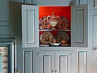 The inside of this cupboard in the blue panelling of the living room has been painted a bright orange, which was a Dutch tradition