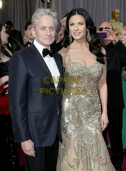 Michael Douglas & Catherine Zeta-Jones (wearing Zuhair Murad).85th Annual Academy Awards held at the Dolby Theatre at Hollywood & Highland Center, Hollywood, California, USA..February 24th, 2013.oscars half length silver gold beige tulle metallic dress sequins sequined beads beaded black trousers blue suit jacket white shirt bow tie married husband wife .CAP/ADM.©AdMedia/Capital Pictures.