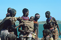 "The El Molo are the smallest ethnic group in Kenya, 25 persons  in the seventy, 200 persons today. For some time now El Molo have been intermingling with their neighbours the Samburu and Turkana, and nowaday no-one still speaks the language of their forebears. They live on lava rock of the southeast shore of Lake Turkana.  Their dwellings resemble "" abandoned nests of ancient prehistoric birds"" (Alberto Moravia)"" , constructed with Dum palm (Hyphaene thebaica) fibres. This tiny population fishes the lake for Nile perch, tilapia:  they occasionally  hunt crocodiles and hippos."