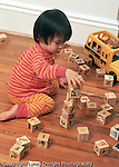 19 month old toddler girl playing with blocks making block tower Asian Vietnamese vertical