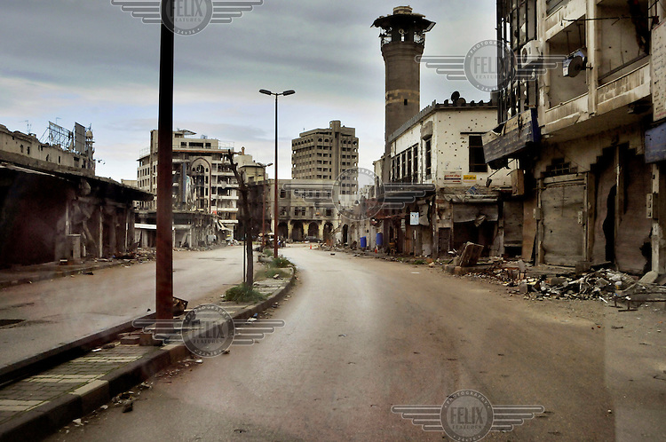A battle damaged street seen through the window of a car. After a three year long battle and siege by government troops, armed opposition fighters left the old centre of Homs, the only part they still occupied, in May 2014. Much of the city has been reduced to ruins by the fighting.