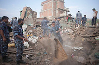 Nepalese police force clears rubble from a destroyed house. Shanku, near Kathmandu, Nepal. May 9, 2015