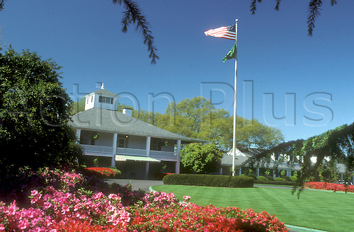 Augusta Golf Course Clubhouse with American flag flying. The Augusta National Golf Club, located in Augusta, Georgia was founded by Bobby Jones and Clifford Roberts on the site of a former indigo plantation, the course was designed by Jones and Alister MacKenzie