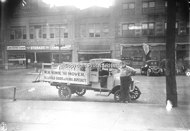 HOWIE THE MOVER. Will H. Howie was photographed with his moving truck on the west side of Government Square around 1923. Howie was born in 1885 to an English mother and Scottish father. He moved pianos and was a driver for various Lincoln transfer companies before operating a business in his own name in the early 1920s. Howie's truck appears to be the Revere model assembled by Hebb Motors of Lincoln. In 1919 and 1920, Hebb manufactured Patriot Trucks on Ford chassis in Havelock, adjacent to Lincoln. <br /> <br /> Photographs taken on black and white glass negatives by African American photographer(s) John Johnson and Earl McWilliams from 1910 to 1925 in Lincoln, Nebraska. Douglas Keister has 280 5x7 glass negatives taken by these photographers. Larger scans available on request.