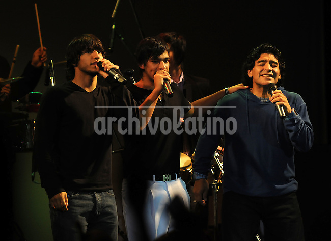 Former Argentine soccer star Diego Maradona gestures next to soccer player Sergio Aguero (L) and an unidentified member of the band Los Leales (C) during their show at Colonial theatre in Avellaneda, on the outskirts of Buenos Aires, late June 27, 2008.