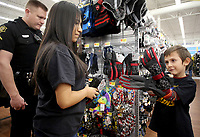 NWA Democrat-Gazette/DAVID GOTTSCHALK School Resource Officer John Robertson (from left), with the Springdale Police Department, and Jennifer Flores, a sophomore at Springdale High School and member of the Law and Public Safety Academy shop Tuesday, December 4, 2018, with Shawn Babin Jr., 6, at the Walmart Supercenter on Pleasant Street in Springdale. More than 200 children participated in the Springdale Police Department Shop with a Cop program. The department collected $45,000 this year for the program.