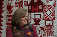"NWA Democrat-Gazette/ANTHONY REYES @NWATONYR<br /> Barbara Hamernik talks Monday, April 3, 2017 backdropped by her quilt ""Farm Girl Goes Red and White"" at the Shiloh Museum in Springdale. The quilt won Judge's Choice and First Place Pieced, Twin/Full Size Category in the Tomorrow's Heirlooms XVI quilt show."