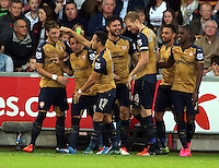 Olivier Giroud of Arsenal (C) celebrates his opening goal with team mates during the Barclays Premier League match between Swansea City and Arsenal at the Liberty Stadium, Swansea on October 31st 2015
