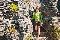 A young woman amongst limestone formations in Punakaiki - Paparoa National Park, West Coast, New Zealand