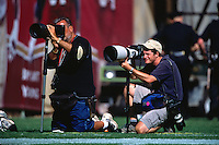 SAN FRANCISCO, CA - Sports photographers Mickey Palmer and Jed Jacobsohn shoot from the sidelines during a football game between the Denver Broncos and San Francisco 49ers at Candlestick Park in San Francisco, California on September 15, 2002. (Photo by Brad Mangin)