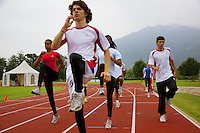 Switzerland. Canton Ticino. Tenero. Centro Sportivo Nazionale della Gioventù - Tenero (CST). Warm-up of men and women teams for the 4 × 100 metres relay. The sprint relay is an athletics track event run in lanes over one lap of the track with four runners completing 100 meters each. A relay baton is carried by each runner and must be passed within a 20 m changeover box (usually marked by yellow lines) which extends 10 m on either side of each 100 m mark of the race. 31.05.11 © 2011 Didier Ruef