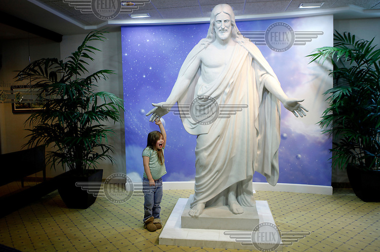 A little girl laughs while she holds the hand of a statue of Jesus Christ at the visitor's centre at the Temple of the Latter Day Saints in Idaho Falls, Idaho.