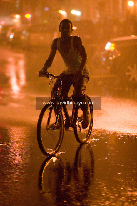 2 August 2006 - New York City, NY - A man cycles through the spray of water gushing from an open fire hydrant in Harlem in New York City, USA, on the hottest day of one of the summer heatwaves.