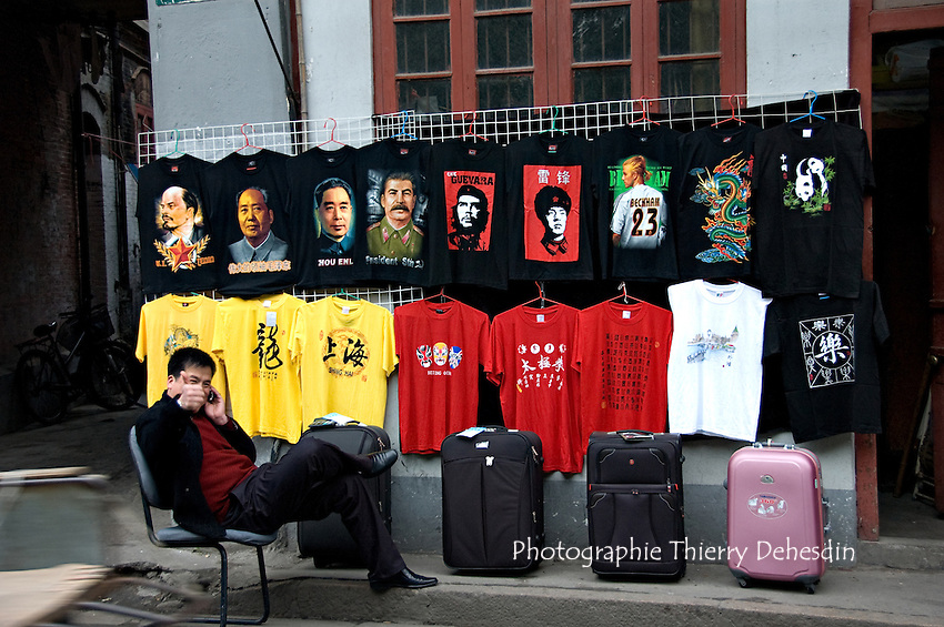 A young happy street vendor selling teeshirts print with faces of communist leaders and a famous english soccer player..Shanghai, February 2006..