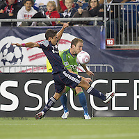 Seattle Sounders defender Tyson Wahl (5) crosses the ball as New England Revolution midfielder Ryan Guy (13) defends. In a Major League Soccer (MLS) match, the Seattle Sounders FC defeated the New England Revolution, 2-1, at Gillette Stadium on October 1, 2011.