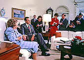 United States President George H.W. Bush speaks to the press pool in the Oval Office of the White House in Washington, D.C. during his first full day as President on January 21, 1989. His mother Dorothy Walker Bush, 87, looks on from the left.  Legendary UPI reporter Helen Thomas is at center, just right of the President.<br /> Credit: Dennis Brack / Pool via CNP