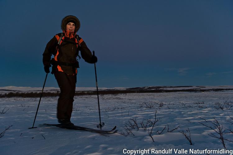 Dame går på ski på vidda i mørketid. ---- Woman skiing in the dark season.