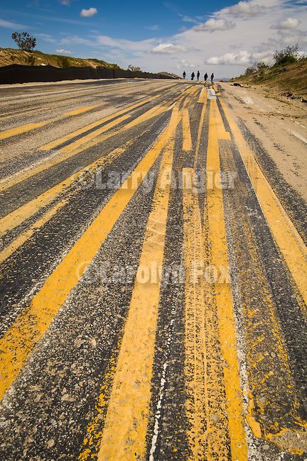 A group of five walkes the road paint striping test area on a paved street, clouds.