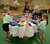 NWA Democrat-Gazette/ANDY SHUPE<br /> Volunteer Kristen Iovinelli (right) helps Blakelee Trimble, 6, to separate packages of socks Saturday, Aug. 10, 2019, during the River Valley Kick Start at Alma Middle School. Inspired by her daughter, Harper, attorney Carrie Jernigan bought all 1,500 pairs of shoes from a closing Payless Shoe Source in Fort Smith. Her effort national publicity and thousands of dollars in donations, which she used to buy more shoes and school supplies for kids going back to school.