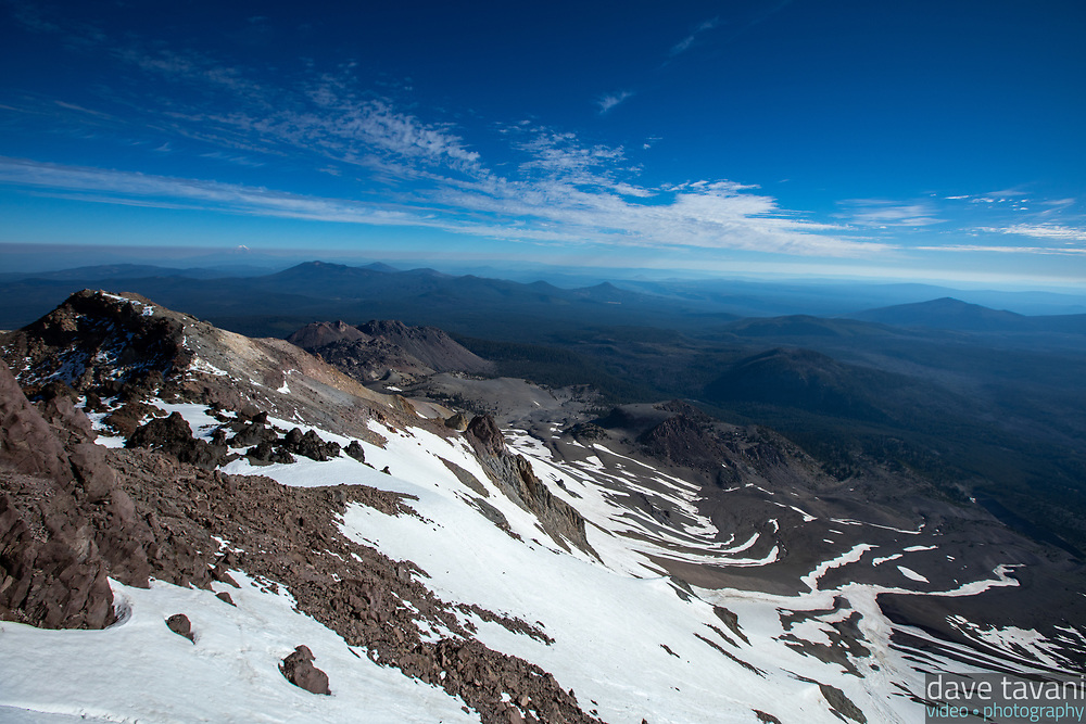 "In 1915, Lassen Peak erupted twice. In this view from the summit, ""The Devastated Area"" can be seen in the bottom right. It is an area where few trees grow more than one hundred years after the eruption and ensuing avalanche that destroyed everything in its path."