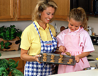 A smiling mother and young daughter making cookies in the the kitchen.