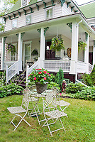 Old Victorian style house with rustic antique recycled garden patio furniture, pots in containers, on lawn grass