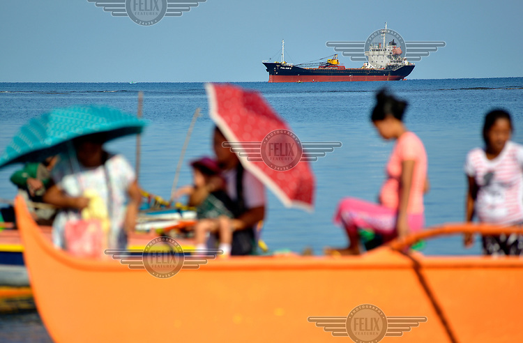 Passengers heading to the fish market arrive on a small ferry. Behind them an oil tanker sits on the horizon.